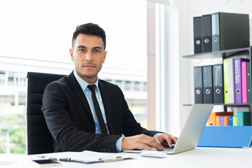 Portrait of a confident businessman working on laptop.