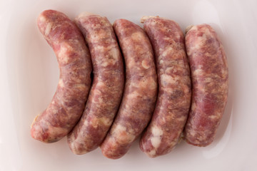 Raw sausages for a barbecue on a white plate. Several barbecue sausages lie next to each other.