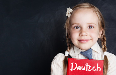 Kids learn German. Curious child girl with german book on chalkboard in language school