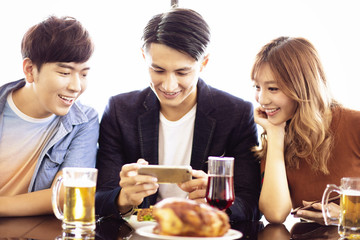 young friends watching the smartphone at restaurant