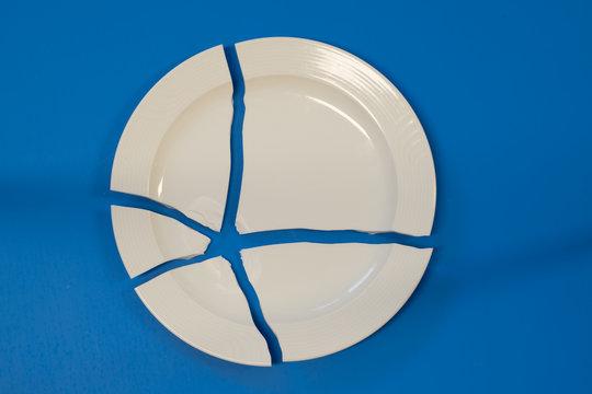 broken porcelain plate on a blue background