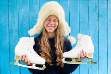 Cheerful little girl in warm sweater and hat keeps figure skates. Blue wooden background.