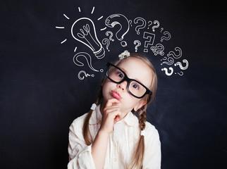Cute child little girl with chalk lightbulb new idea symbol . Kid ideas and brainstorm