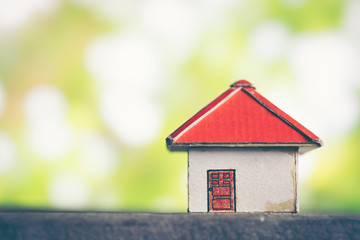 model of cardboard house against green bokeh background. building, loan, real estate or buying a new home concept.