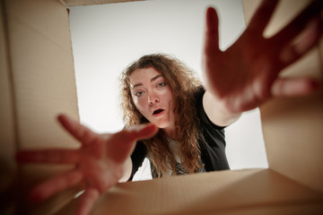 The surprised woman opening box and looking inside. The package, delivery, surprise, gift, lifestyle concept. Human emotions concepts