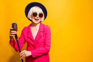 Portrait of happy old woman holding a microphone stand and singi Fototapete