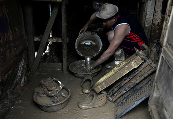 A resident washes kitchen items in his swamped by mud house  after flash floods in San Mateo, Rizal