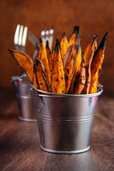 Wall Mural - Homemade baked sweet potato fries with skin in  metal serving bucket on wooden background
