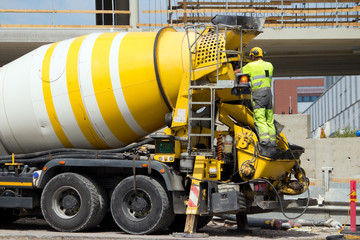 Construction site worker washing concrete truck