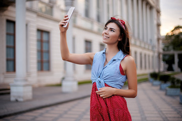 Portrait of wonderful caucasian woman taking selfie with smartphone in Europe. Brunette female hipster with piercing in nose making self portrait with cellphone camera on european street on vacation.