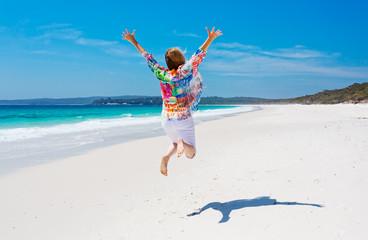 Summertime woman jump for joy beach