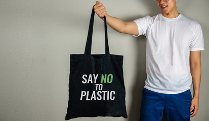 Say no to plastic text on tote bag carrying by man