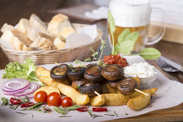 Appetizing vegetables cooked on the grill. Barbecue mushrooms and potatoes.  Tasty snack