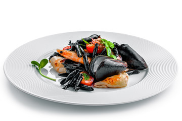 High class healthy Italian seafood pasta meal isolated on white background.. Black squid ink strozzaperti with shrimp and mussels on a plate.