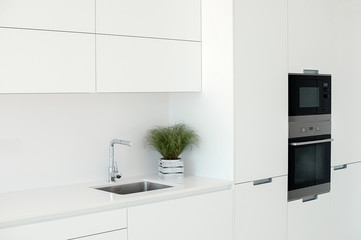 White kitchen interior. Minimalistic interior design. Modern furniture and built-in appliances.