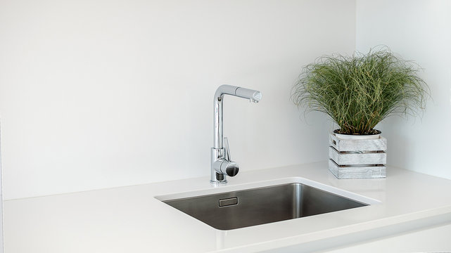 Modern kitchen sink and faucet with decorative flowers.