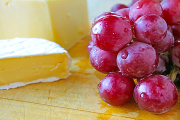 Fresh dark read grapes served with cheese on a wooden board
