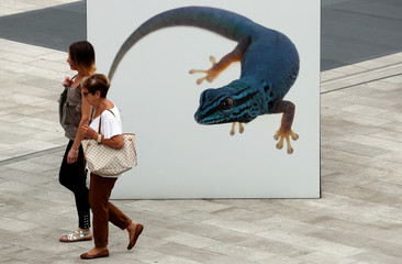Two women stroll in front of an eletric blue gecko picture, part of a street exhibition, in Milan