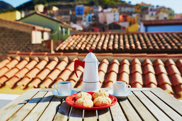 Coffee and Italian sweets with view to Bosa village, Sardinia, Italy