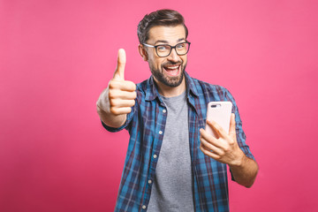 Portrait of a cheerful bearded man taking selfie and showing thumbs up gesture over pink background. Isolated.