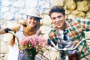 Young beautiful couple riding bikes in summer