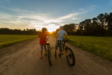 childs riding one bike together on sunny summer evening. sitting on bicycle rack. Family of two people enjoying traveling in scenic field over sunset sky background.