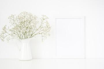 White frame mockup A4 in interior. Frame mock up background for poster or photo frame for bloggers, social media, lettering, art and design. Indoor, frame on table with flowers in vase. Poster mock up