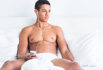 Young handsome topless black man enjoying music in bed.
