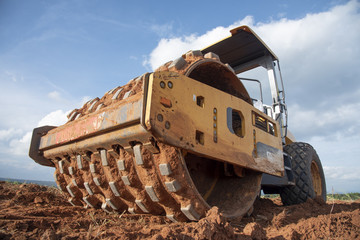 Yellow vibratory soil compactor working on highway construction site