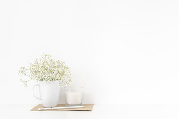 Background with stationary, white candle, pencil and bouquet of white flowers in mug on white wall background, summer home decor. Copy space for text. Empty space for lettering.
