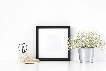 Black square photo frame and supplies on table and vase with white flowers near white wall. Hipster minimalism loft desk space, copy space. Background