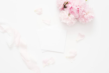 Elegant feminine wedding or birthday flat lay composition with pink peonies floral bouquet and silk ribbon. Blank paper card, mockup, invitations. Flatlay, top view.