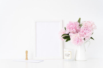 White a4 blank frame mockup. Still life composition, floral bouquet of pink peonies in jug, gold stamp and con. Background, mock up for quote, promotion, headline, design, lifestyle bloggers