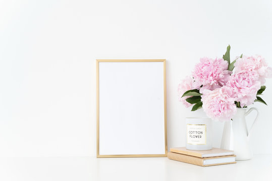 Elegant gold portrait a4 frame mock up with a pink peonies in white jug. Overlay your quote, promotion, headline, or design, great for small businesses, lifestyle bloggers and social media campaigns