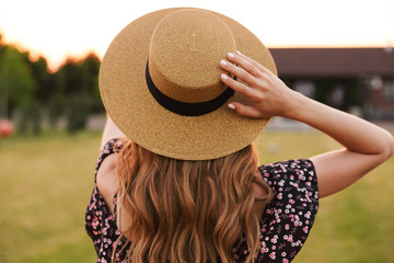 Portrait from back of european woman 20s wearing straw hat and dress, walking outdoor on nature in countryside