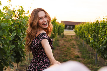 Pretty young woman holding hand of her boyfriend while walking outdoor together, through vineyard on summer day. Follow me concept Fototapete
