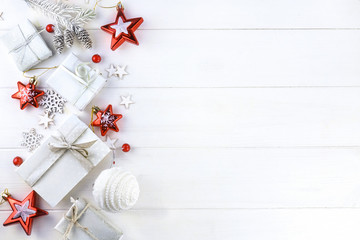 Christmas composition, border in light colors. Christmas gift, fir branches and cones, stars and snowflakes on wooden white background, top view. Flat lay, copy space.