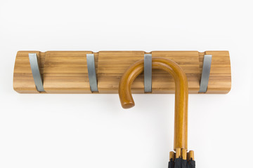 Wood hook rack with umbrella isolated on white background, home concept