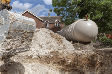A Excuvator crawler digging a trench for an underground tank on a housing development in Hampshire, England, UK