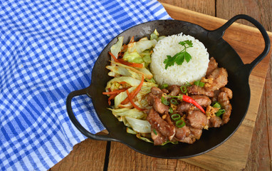 Fried sliced pork with garlic and pepper  served with Fried vegetable and Thai rice in small wok.