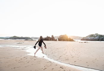 Anonymous woman jumping over brook on beach