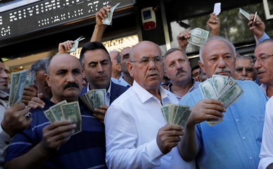 Businessmen holding U.S. dollars stand in front of a currency exchange office in Ankara