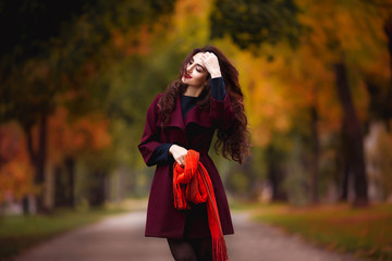 Happy young woman in park on sunny autumn day. Cheerful beautiful girl in red coat and scarf outdoors among yellow leaves on beautiful fall day.