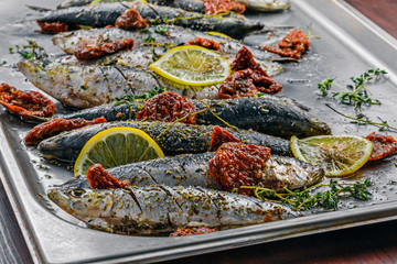Raw sardine fish on a baking tray. Cooking of delicious seafood meal in an  oven. Close-up shot.