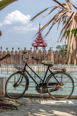 An old bicycle is lean on a railing over a water moat before the Royal Palace in Mandalay, Myanmar.