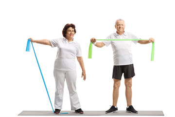 Elderly woman and an elderly man working out with rubber bands