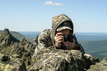 girl wildlife photographer in camouflage suit in the mountains hiding behind a stone photographing something