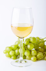 A glass of white wine with a bunch of green grapes on a white background. Alcoholic beverages.