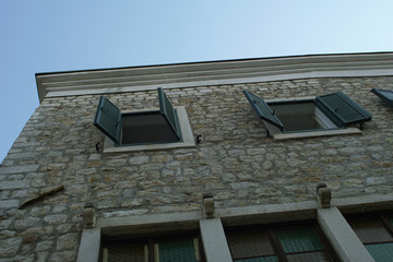 Traditional house made from stone, with a green wooden window covers