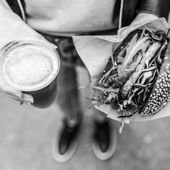 Close Up Of Woman Hands Holding Delicious Organic Salmon Vegetarian Burger and Homebrewed IPA Beer on Open Air Beer an Burger UrbanStreet Food Festival. Black and white image.